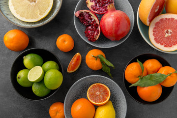 food, healthy eating and vegetarian concept - close up of citrus fruits in bowls on stone table