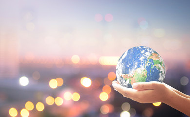 Corporate social responsibility (CSR) concept: Human hands holding earth globe over blurred city background. Elements of this image furnished by NASA