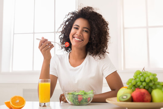 African-american woman with vegetable salad and fresh juice
