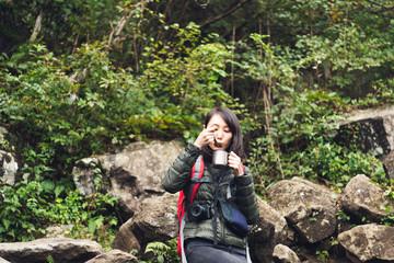 ハイキングの休憩中にスープを飲む女性
