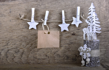 paper sign for message and  white stars hung at a string on wooden background