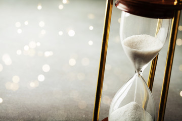 Sand running through the hourglass. Time keeper concept. Boke effect.