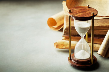 Sand running through the hourglass and old vintage books. Time keeper concept.