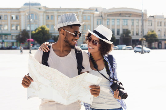 Loving african-american couple traveling and reading map in city