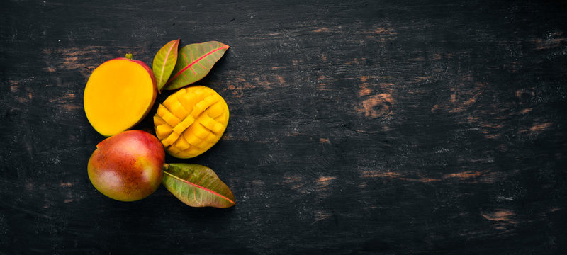 Mango with leaves on a black wooden background. Tropical Fruits. Top view. free space for your text.