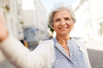 old age, retirement and people concept - happy senior woman taking selfie on city street in summer