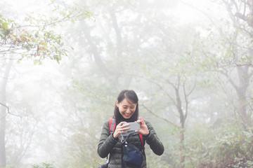 ハイキング中に携帯で写真を撮り笑っている女性