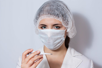 Woman doctor in a protective mask with an electronic thermometer in hand. Measurement of body temperature.