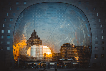 Reflection of cityscape in Rotterdam on the facade of Market Hall (Markthal) during golden hour