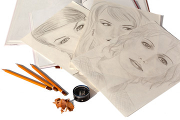 Portraits of women drawn in pencil on sheets of paper, notebook, three pencils, pencil sharpener, eraser on a white background isolated top view