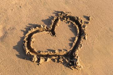 Heart shape on the sand at the sea beach.