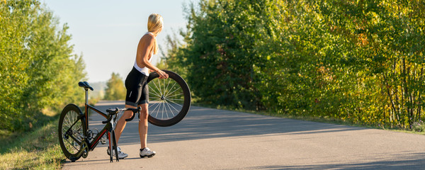 Papiers peints Cyclisme Sexy girl with a road bike and a flat tire looking for help panorama