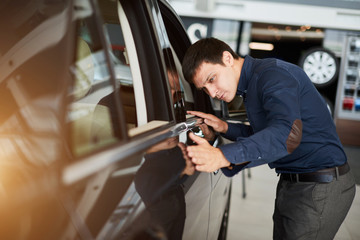 Professional salesman checking out interior and design of a new car at the dealership car, dealer helping his customer to buy luxury vehicle