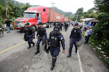 Honduran police officers are seen at the Agua Caliente border with Guatemala while waiting for groups of Honduras' migrants trying to join a migrant caravan heading to the U.S., in the municipality of Ocotepeque