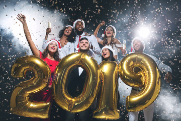 1bf27a92ce44e Multiethnic friends holding 2019 balloons at New Year party
