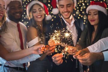 Friends in New Year eve with sparkling bengal lights