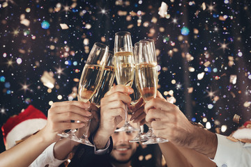 Clinking glasses of champagne in hands at New Year party
