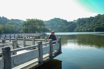 Senior women tourist stand beside the Lake on top of the xiqiao mountain foshan city china