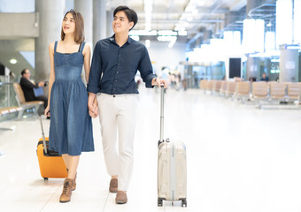 Young smiling Asian couple with luggage walking in the airport. Lover travel and transportation concept.