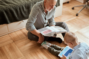 Mature man looking photo book and his grandson using digital tablet