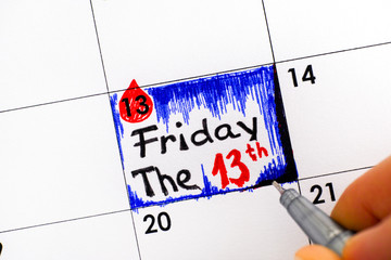 Woman fingers with pen writing reminder Friday The 13th in calendar.