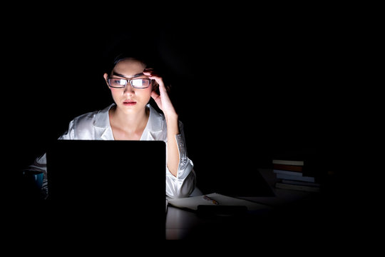 Woman working late at her home office.