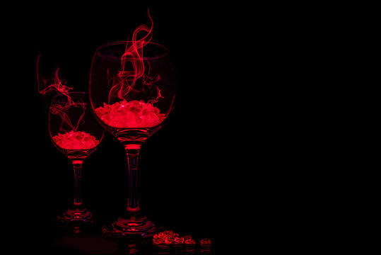 Glowing red drink in wine glasses with red smoke