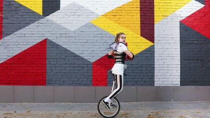 Wall Mural - Girl clown with a holiday gift in her hands riding a unicycle outdoors