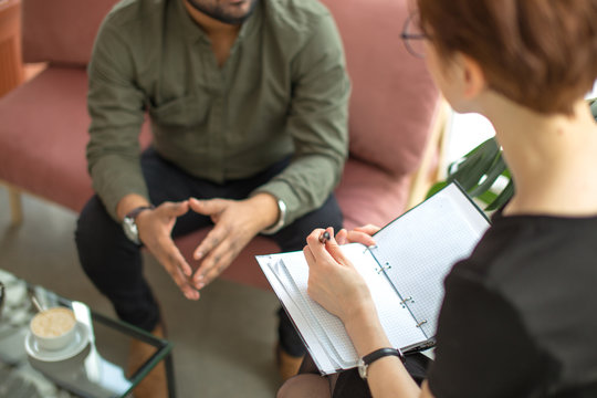 psychotherapist consulting man, asking questions, interviewing man sitting on sofa. psychologist with client