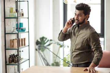 Indian businessman talking on phone in modern office