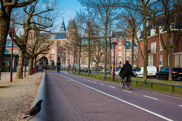 Cyclists at the bikeway next to the National Museum of Amsterdam in a cold early spring day