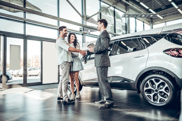 Young couple shaking hands with sales agent after a successful car buying Wall mural