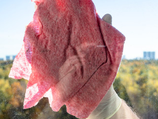 pink rag close up cleans window glass