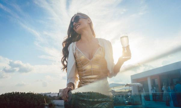 Frau trinkt Glas Sekt auf einer Party im Sommer
