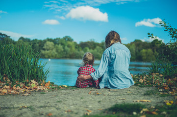 Mother and toddler relaxing by pond in forest