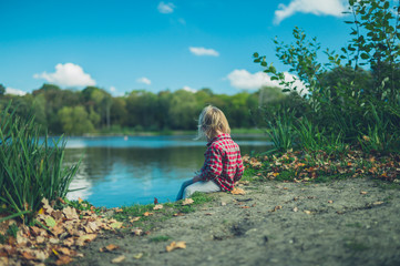 Little toddler sitting by a pond in the forest