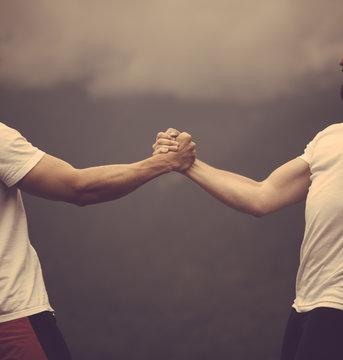 Two crossfit sports men doing arm wrestling exercise during outdoor workout against cloudy sky background. Hands together - fitness team after training.