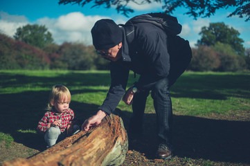 Toddler and grandfather looking at a log