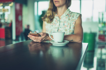 Young woman drinking coffee and using smartphone in airport