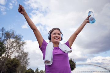 Fitness woman holding bottle of water and towel