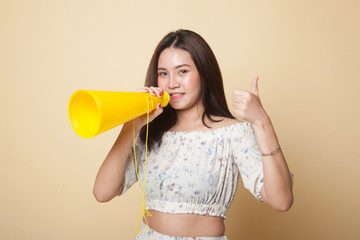 Beautiful young Asian woman show thumbs up announce with megaphone.