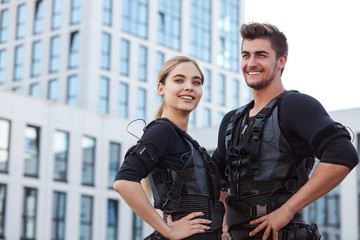 two positive young people wearing ems fitness vest and posing to the camera on the street.copy space