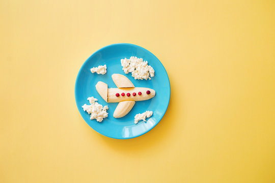 Fun food idea for kids. children's Breakfast: plane made of banana and clouds made of curd on a blue plate. dreams of flying. creative lunch of the future pilot