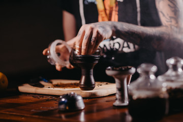 The process of cooking shisha, hookah bowl.Fruit in ice shaking.Citrus fruit for Shisha.Tattooed hands