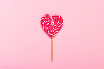 Lollipop on a gently pink background. Heart shape. Flat lay, top