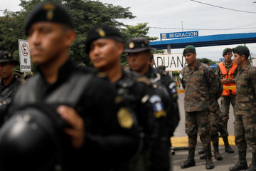Police officers stand in line in front of the border checkpoint between Guatemala and Mexico, in Tecun Uman