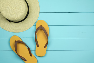 Straw hat and flip flops on light green wooden background.