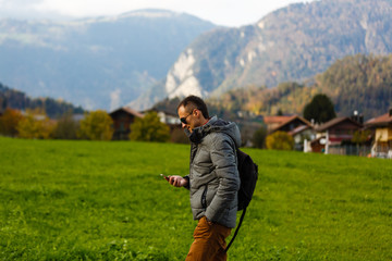 Wall Mural - A man turist with a gadget walking on a rural path in Swiss Alps