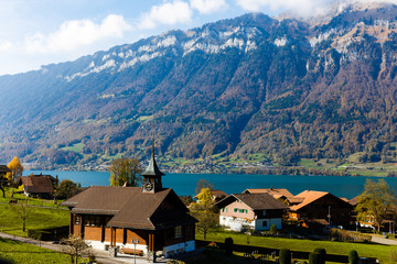 Wall Mural - Picturesque alpine meadows, chalets, lake and church with a clocktower in the Swiss Alps