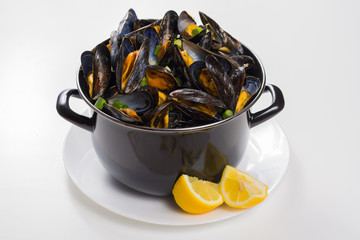 Black pan with cooked with green onion, parsley marinated high quality mussels